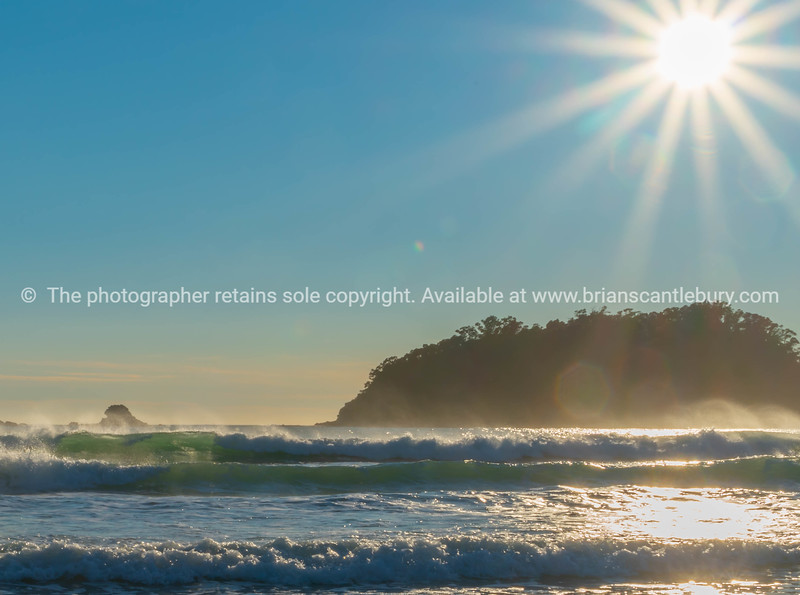 Lens flare, stunning over rocky coastal edge