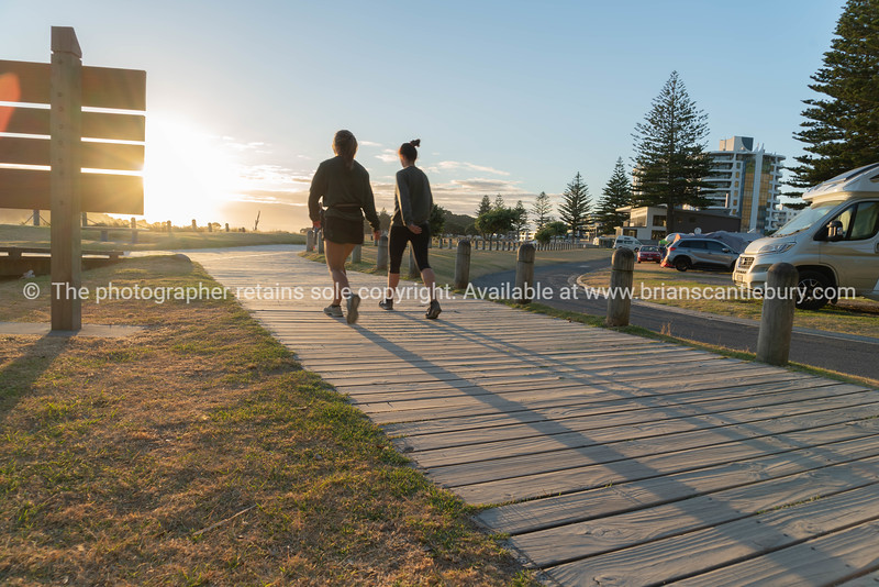 Early start to day walkers out on Mount boardwalk cast long shadows as sun rises,