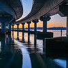 Curving lines and calm water under Tauranga Harbour Bridge at sunrise.