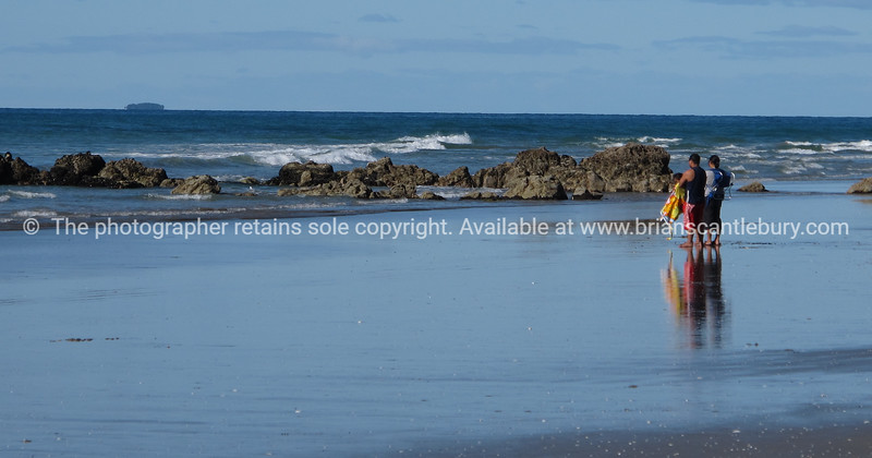 """Beach scene, two people on Mount Maunganui's oceanbeach, New Zealand. Tauranga is New Zealands 5th largest city and offers a wonderfull variety of scenic and cultural experiences. Tauranga stock images Tauranga scenics.<br /> Model Release; no. See;  <a href=""""http://www.blurb.com/b/3811392-tauranga"""">http://www.blurb.com/b/3811392-tauranga</a> mount maunganui landscape photography, Tauranga Photos; Tauranga photos, Photos of Tauranga Also see; <a href=""""http://www.brianscantlebury.com/Events"""">http://www.brianscantlebury.com/Events</a>"""