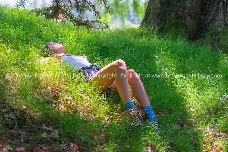 Teenage girl lying in green grass
