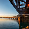 Sunrise across Tauranga harbour catches historic railway bridge.