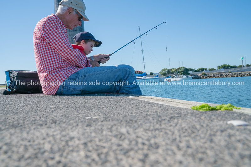Grandfather and grandson sitting together on pier