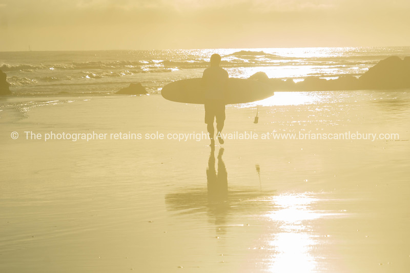 Background faded image of surfer walking into sunrise and water carrying surfboard.
