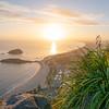 Sun on horizon illuminates long Mount Maunganui coast