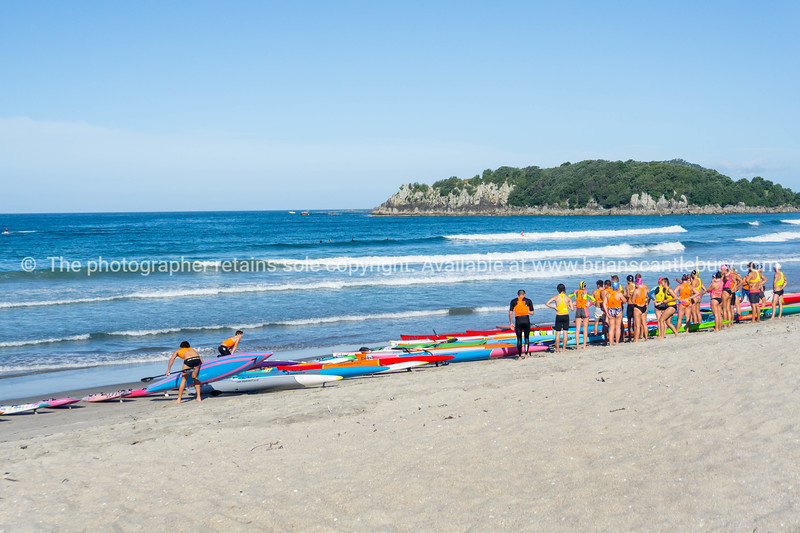 Large group young fit people in their vibrant swim suits gather on beach with surf skis preparing to go paddling in ocean water