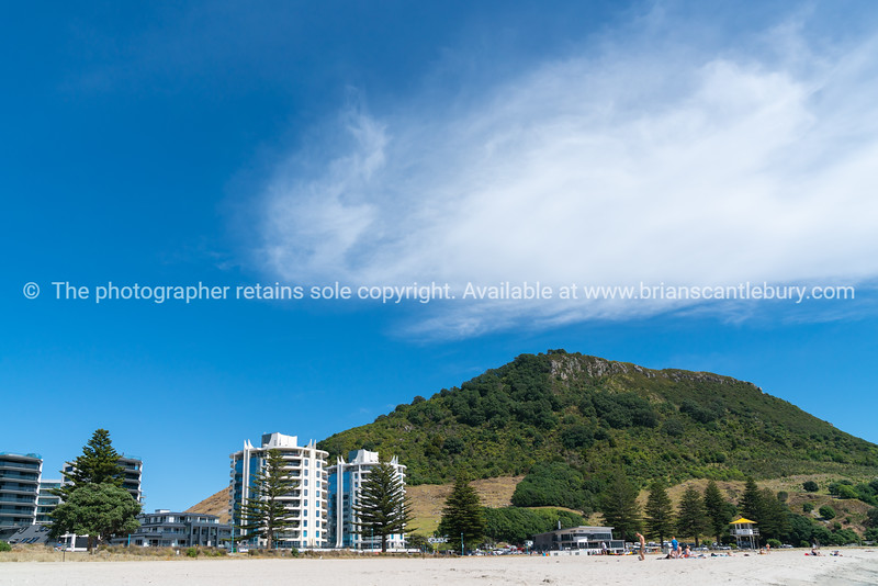 Oceanside Twin Tower apartments on Mount Main Beach in background to people enjoying summer beach day.