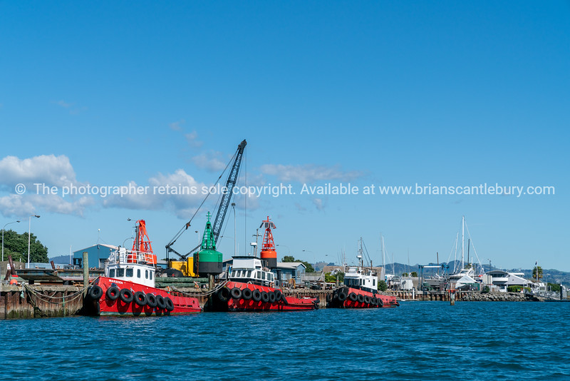Three red harbour maintenance boats alongside dock