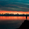 Vibrant sunrise across bay with with silhouette of  figure of person