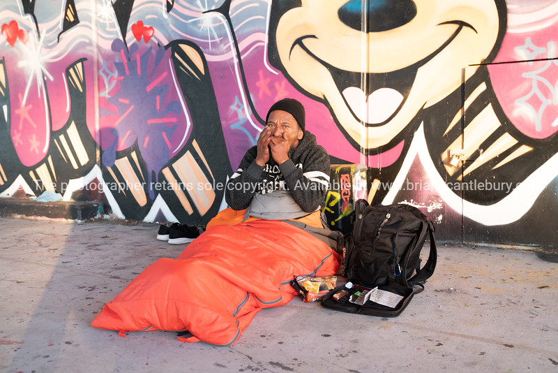 Homeless man by name of John early moring in his orange sleeping bag under tauranga Harbour Bridge