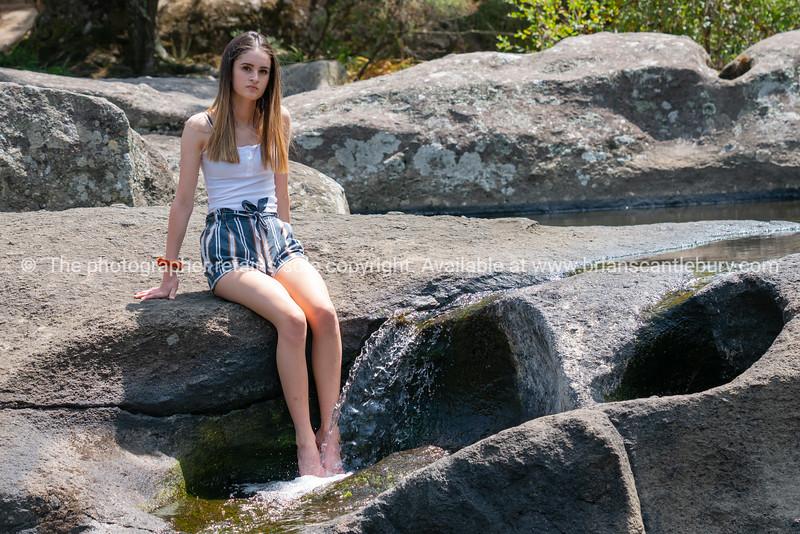 Attractive teenage girl sitting on rock ledge with legs splashing cool water