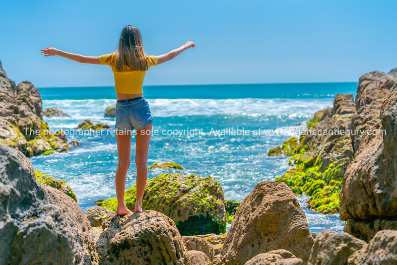 Girl in yellow top on coastal rocky seaside.
