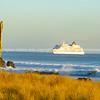 Small cruise ship approached Tauranga harbor entrance at base of Mount Maunganui
