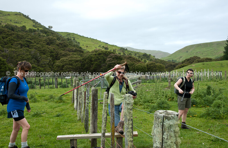 Three women cross a stile on Tora Walk. New Zealand Image.