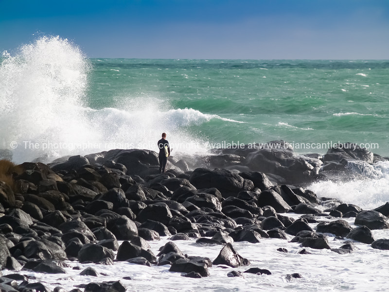 Lone surfer stands holding his board waiting for moment to jump from rocks and boulders into surf.