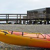 Brightly coloured kayak forms foreground to Okarito wharf, West Coast, South Island, New Zealand. New Zealand photographic stock images. South Island