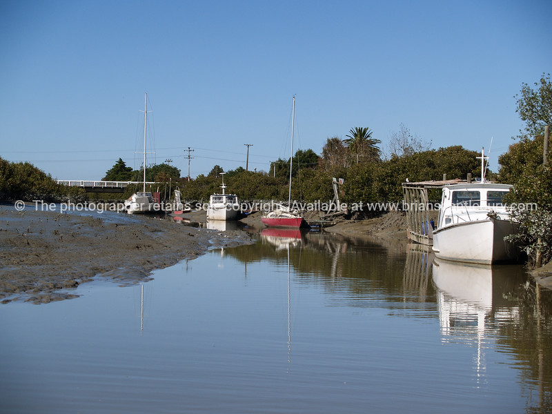 Boats moored in the muddy Waitakaruru River, Waikato, New Zealand.