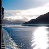 Sea, sun, and rolling hills from a ship. New Zealand images.