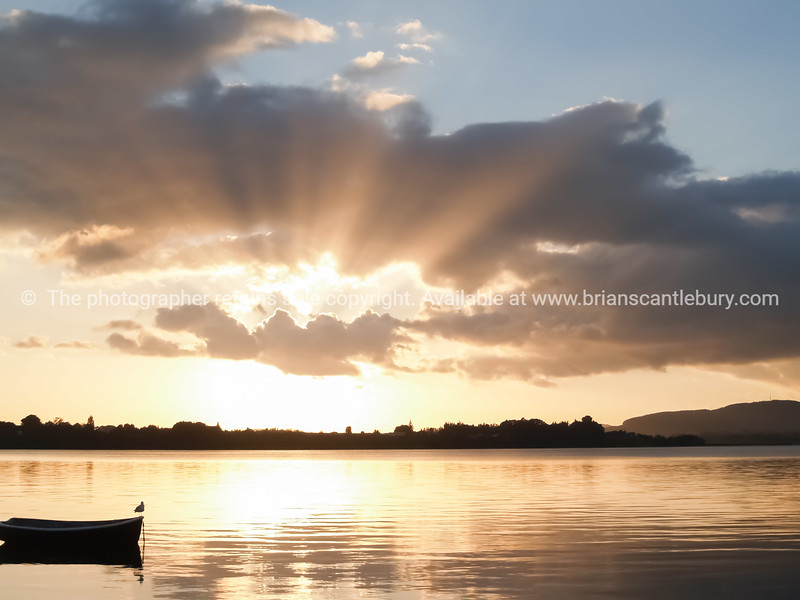 Sun bursts through clouds over small dinghy