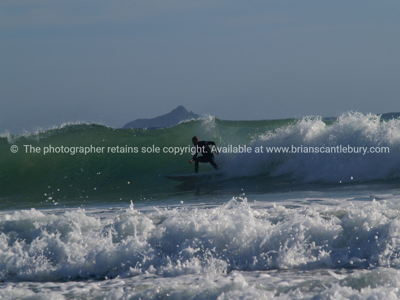 "Surfer carving across a wave on Mount Maungaui's oceanbeach. Mayor Island on the horizon. Tauranga is New Zealands 5th largest city and offers a wonderfull variety of scenic and cultural experiences. Tauranga stock images Tauranga scenics. See;  <a href=""http://www.blurb.com/b/3811392-tauranga"">http://www.blurb.com/b/3811392-tauranga</a> mount maunganui landscape photography, Tauranga Photos; Tauranga photos, Photos of Tauranga Also see; <a href=""http://www.brianscantlebury.com/Events"">http://www.brianscantlebury.com/Events</a>"