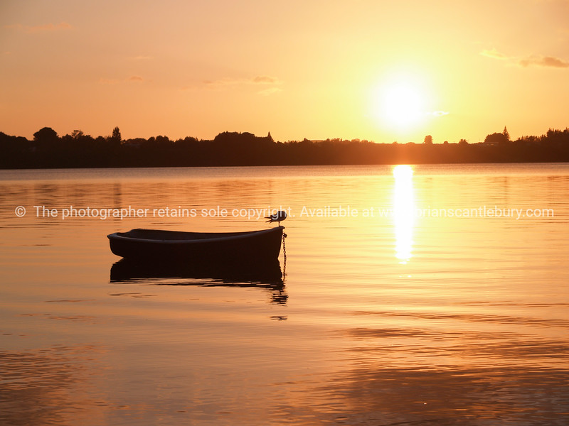 Small dinghy afloat and silhouetted on red harbour water at sunrise