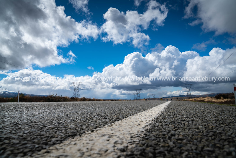 High voltage power distribution lines run parallel alongside Desert Road North Island land and cloud scapes