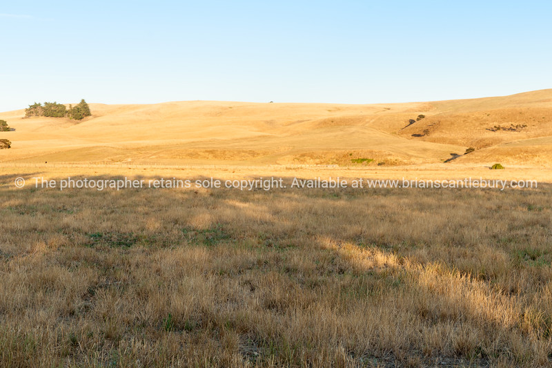 Rising sun hits rolling hills before crossing the dry plains.