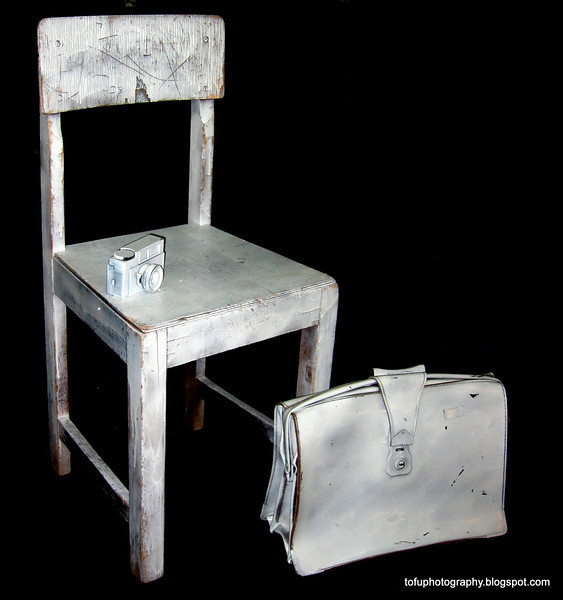 A chair, a satchel and a camera in the window of a gallery in Christchurch, New Zealand in November 2010