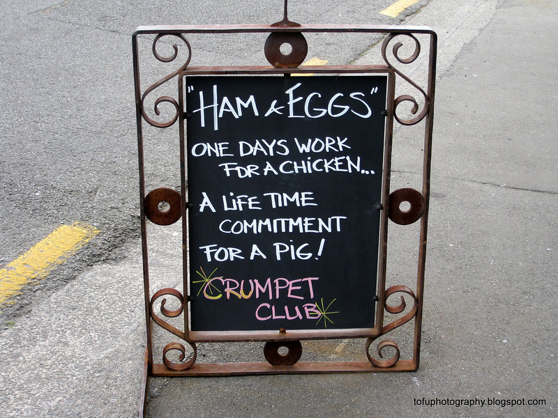 Crumpet Club cafe sign in Christchurch, New Zealand in November 2010. Ham and Eggs. One days work for a chicken, a life time commitment for a pig!