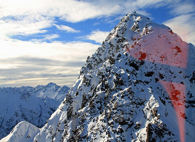 Consolation Peak (1759m amsl) with Automatic Weather Station on the summit.  (The red colouring is a reflection on the helicopter window from inside).