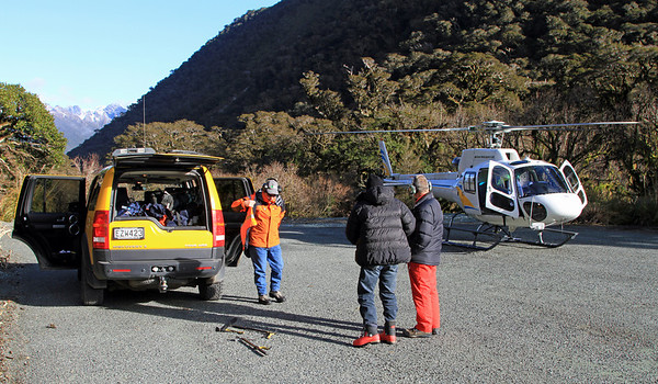 Departure from the car park at the divide - Wayne Carran (orange jacket), Paul Mallinson (black jacket) and helicopter pilot (red overalls).