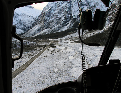 View through the front window of the helicopter of the Milford Road in the upper Hollyford Valley heading towards Homer Tunnel.