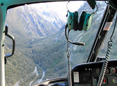View through the front window of the helicopter of Milford Road at the lower end of Hollyford Valley at the turnoff to Lower Hollyford.