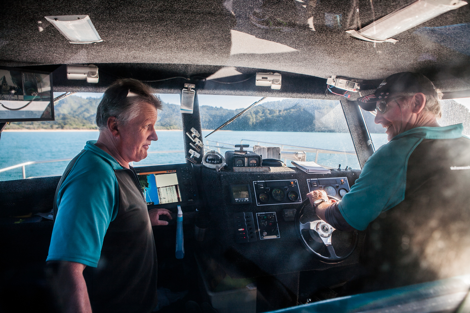 Captains of our sea shuttle discussing the weather conditions in Abel Tasman National Park, New Zealand
