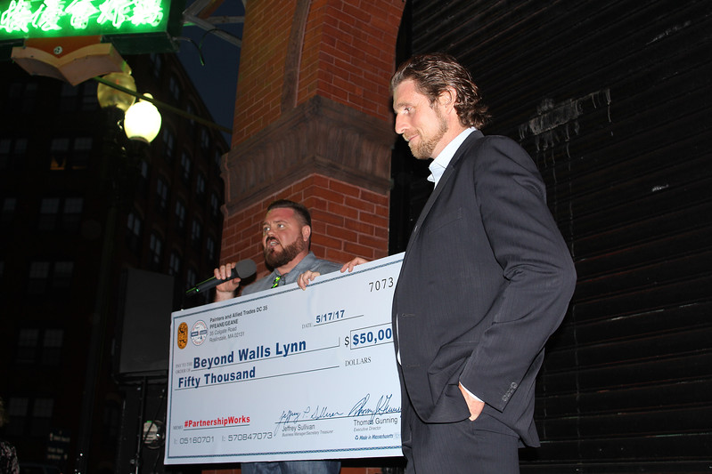 Lynn, Ma. 5-17-17. John Doherty, Director of Communications Painters & Allied Trades DC 35, left, presents a check for fifty thousand dollars to Al Wilson, right, founder and Executive Director of Beyond Walls at the lighting ceremony at the Prime Manufacturing Co. at 545 Washington Street.