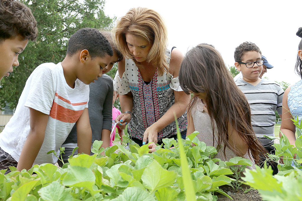 """. A new community garden, they are calling \""""Shelbie\'s Seed of Promise,\"""" was recently planted at Father Maguires Park in memory of Shelbie Murphy. Second grade students from McAvinnue Elementary School work with Shelbie\'s mom Jackie Murphy as they check out the garden Friday. SUN/JOHN LOVE"""
