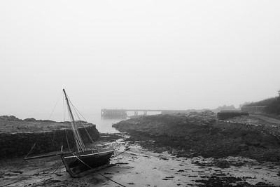 Yacht on beach as tide goes out and a freezing mist come in. Black & White