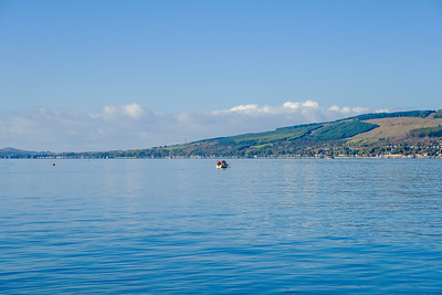 Two Men in a Small Boat on the River Clyde Looking over to Inellan from Inverkip Point Scotland in October.