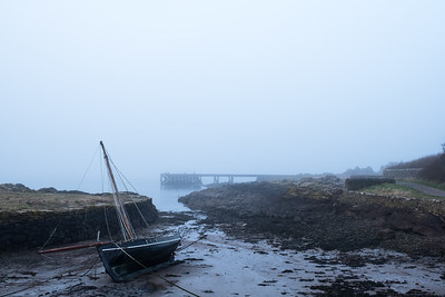 Yacht on beach as tide goes out and a freezing mist come in.