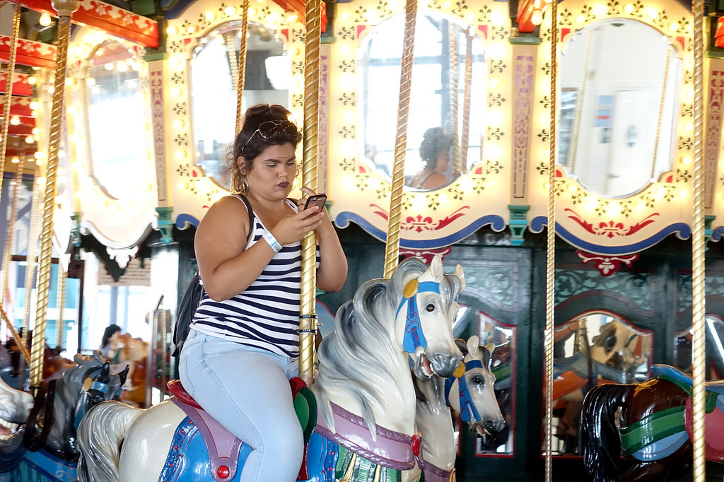 Checking the phone on the merry-go-round