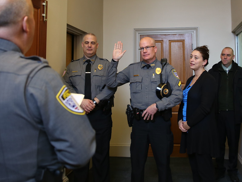 HOLLY PELCZYNSKI - BENNINGTON BANNER Corporal Roscoe Harrington raises his right hand as he is promoted to the rank of Sergeant on Friday morning surrounded by his family and colleagues as well  as Lieutenant Camillo Grande and Chief Paul Doucette.