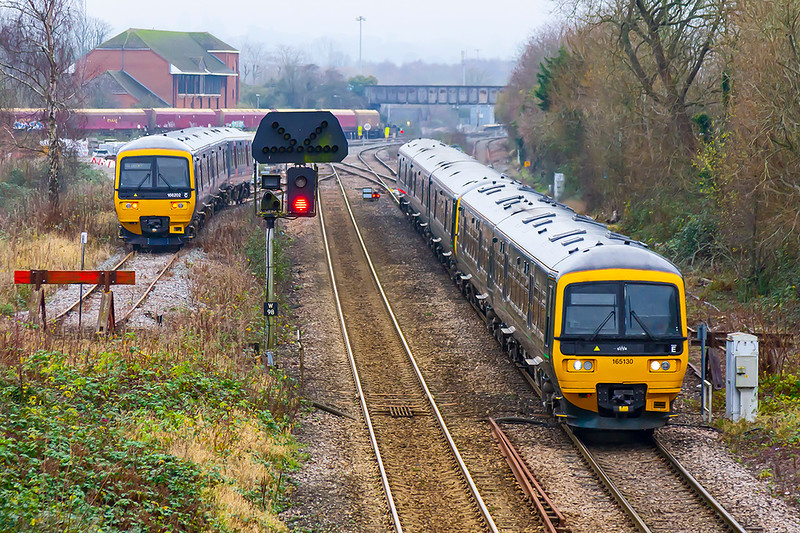 7th Dec 2020: On a very cold morning captured leaving Westbury is 165130 the leading unit on 1F18 the 10.23 from Portsmouth Harbour  to Cardiff;  166202 is sitting in the short siding awaiting it's  next duty. The old coal trucks,  in front of the signal box,  are waiting to be taken away for scrap.