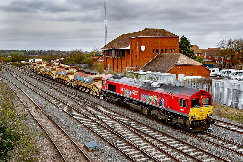 28th Mar 2021:  Passing the Power Signal Box as it arrives at Westbury is the 09.33 from Acton West with 66113 leading.  This loco carries thw branding 'Delivering For Our Key Workers' and showing pictures of 30n workers who could be involed in working during the Covid Pandemic,  66177 is on the other end.