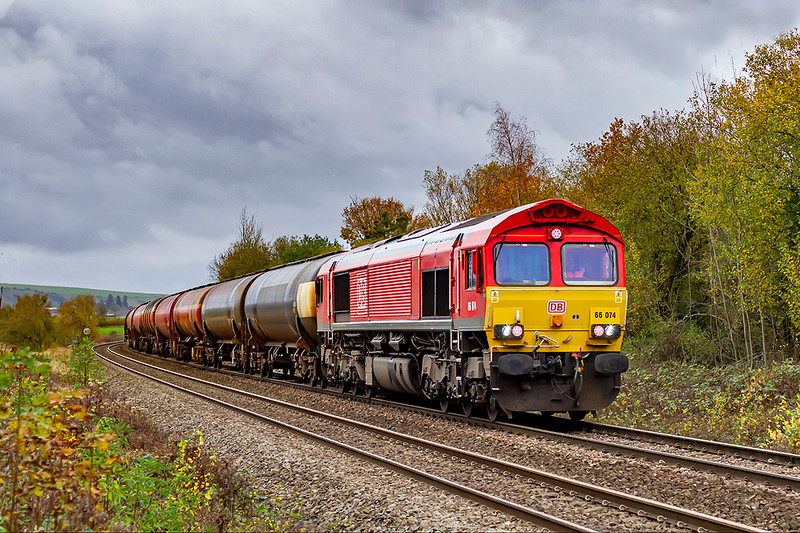 11th Nov 2020:  Not the nicest weather in which to picture a train but I did because I could without being in contact with anyone else and because it was a 66 on the tanks.  Accelerating away from Hawkeridge Junction is 66074 in charge of 6B33 the empty  tanks to Robeston from Theale,.   Interestingly  the loco  carries a BR  '9D'  shed plate  that was for Buxton.   Pictured from the fooot crossing.