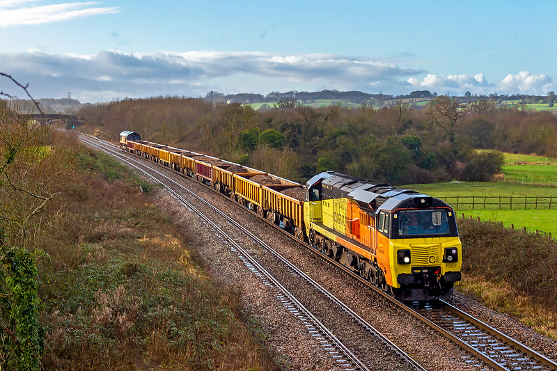12th Jan 2020:  The strong wind was just clearing the rain clouds and letting  the sun appear as 70807 slows to stop at Signal W105 in Fairwood.  6C22 is running from Exeter Riverside to Westbury Down Yard. 66849 is at the other end.
