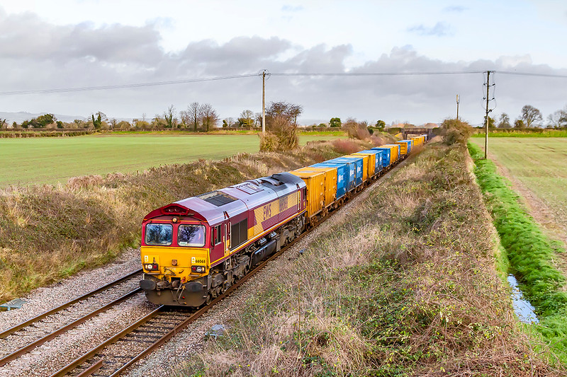 23rd Dec 2019:  66068 is powering 6C03 the rubbish rain from Northolt Sidings to Severside SITA through Edington on the Berks & Hants line. The morning sun departed 5 minutes before the train came