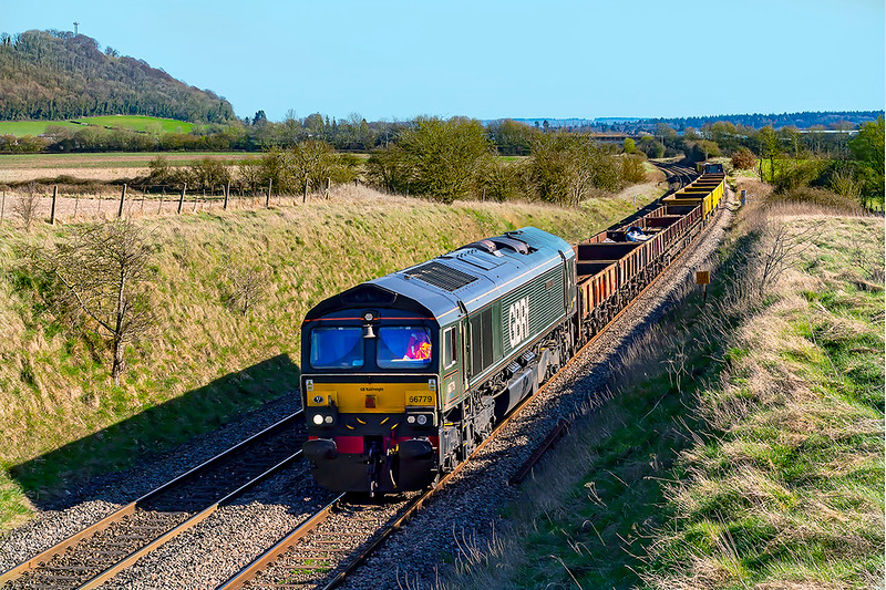 29th Mar 2021:  On a beautifully Suuny and warm afternoon 66779 'Evening Star' is tasked with working t6V41 the afternoon departmental to Westbury from Eastleigh..  The picture is taken from. the farm bridge at the start of the drop down from Upton Scudamore to Westbury.  Arn Hill is visible on the left.