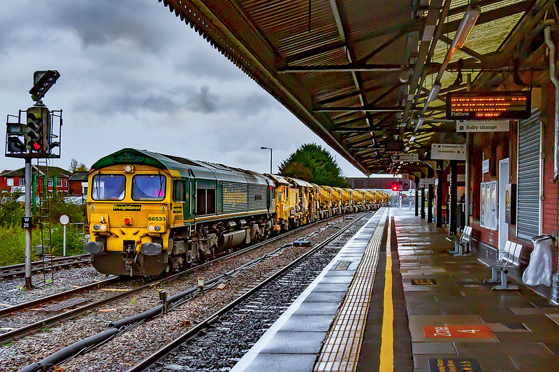 14th Nov 2020:  On a very wet and windy morning at Westbury Station 66533 'Senator Express' ( he other side is named 'Hanjin Express')  entering the Up Loop next to a deserted Platform 3.   6Z72 has come from Fairwater Yard in Taunton vis Bristol, because of engineering works near Castle Cary, so that the HOBC waggons can be refilled with track ballast.