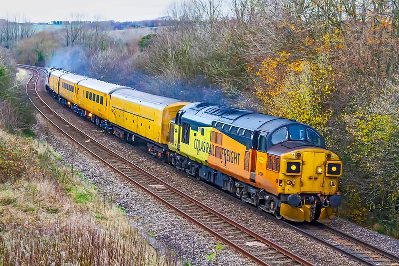 19th Nov 2020:  Now with the sun totally masked by a thick cloud bank 1Q23 is pictured at Sherrington with 37099 'Merl Evans 1947-2015' leading. asit hear=ds to Salisbury . Had the sun been out the whote scene would have been in shaddow. .  They did sound good so it was worth the effort to get the pic as a memory.