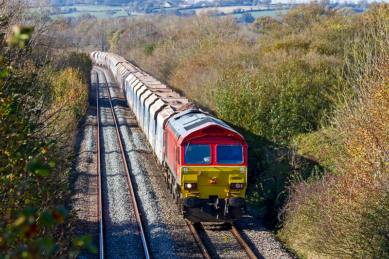 7th Nov 2020:  Belting along the 1933 built Westbury Avoider  is 59204 at the helm of 7A17 from Merehead to Colnbrook.  Virtually all the mainlines in this area have had all the undergrowth cut back and retrimming done as required but nothing at all on this stretch  of line.  Seems odd to me.